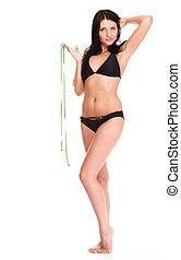 brunette girl bikini measuring waistline tape - young...