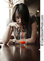 Brunette girl drinking red juice through straw. Shallow DOF.