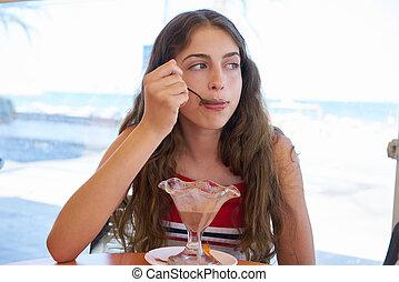 Brunette girl eating chocolate ice cream