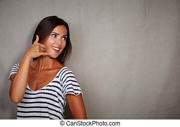 Brunette girl gesturing a call while looking away