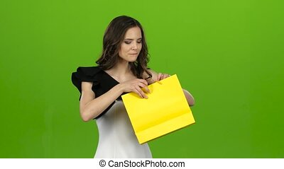 Brunette girl holds a gift bag in her hands, she likes it. Green screen