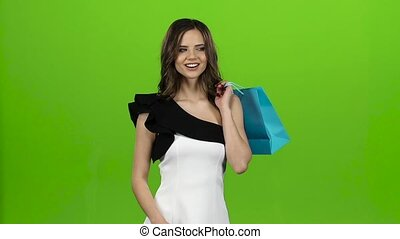 Brunette girl holds a gift bag in her hands, she likes it. Green screen. Slow motion