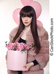 Brunette girl holiday portrait. Fashionable woman in pink fur coat with rose bouquet of flowers in hat box over balloons isolated on white studio background.