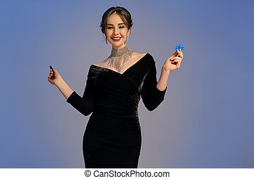 Brunette girl in black dress and shiny jewelry. Smiling, showing two blue and green chips, posing on purple background. Poker, casino. Close-up