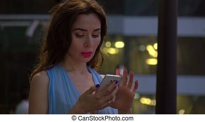Brunette girl in blue dress talking on her smartphone on the street at night. 4K shot