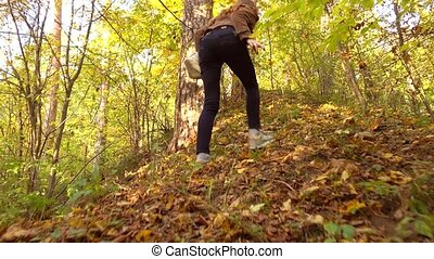 Brunette girl in brown jacket hiking in sunny autumn woods....
