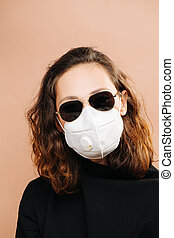 Brunette girl in dark glasses and a protective medical mask with a valve
