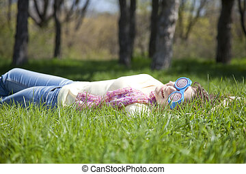 Brunette girl in funny glasses lies at meadow.
