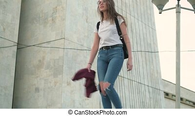 Brunette girl in glasses and torn jeans walking around the...