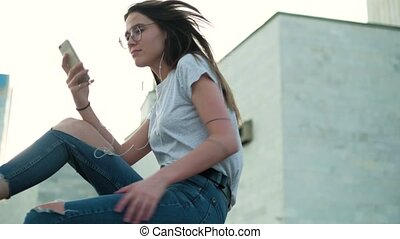 Brunette girl in glasses sits at sunset listens to music and reads messages