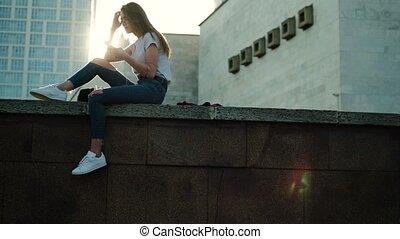 Brunette girl in glasses sits at sunset listens to music straightens hair