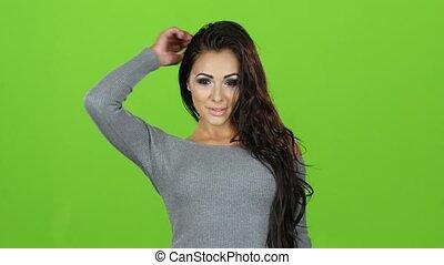 Brunette girl in gray sweater posing on camera, green screen