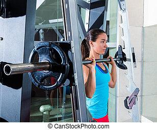 brunette girl in multipower barbell Smith machine
