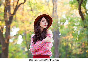 Brunette girl in pink sweater in the autumn park.