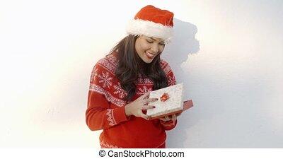 Brunette Girl in Santa Claus Hat Opening Gift