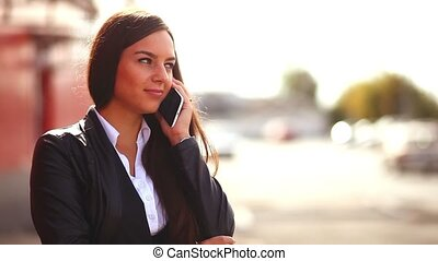 brunette girl in street talking on phone smiling woman behind the outside red background