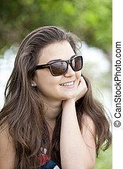 Brunette girl in sunglasses at the summer park.
