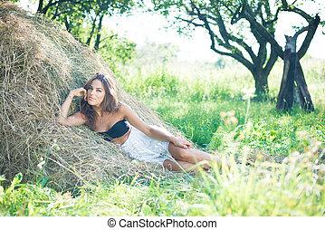 Brunette girl is lying on haystack in summer sunny day