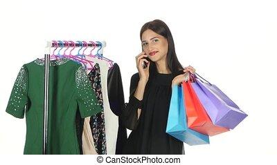 Brunette girl is shopping for dresses while speaking on the...