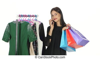 Brunette girl is shopping for dresses while speaking on the...