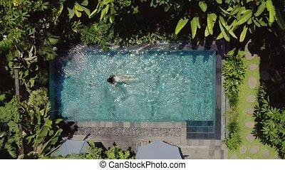 Brunette girl is swimming in outdoor pool on villa between...