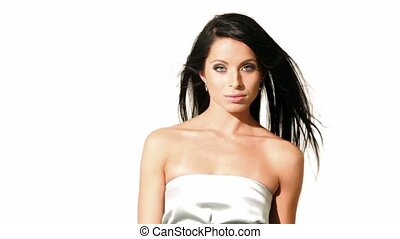 Brunette girl looks and smile, wind flutters her hair