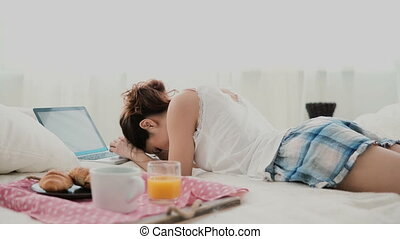 Brunette girl lying on bed in morning and chatting, using laptop for that. Young woman typing on keyboard and laughing.
