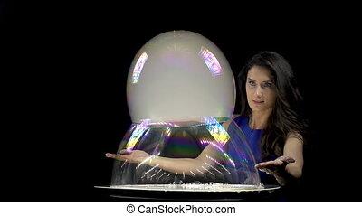 Brunette girl making large soap bubbles