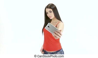 Brunette girl model makes selfie photo on the mobile. Studio