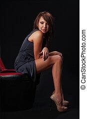 brunette girl posing in studio on dark background