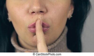 Brunette girl puts finger to her mouth, urging silent. HD