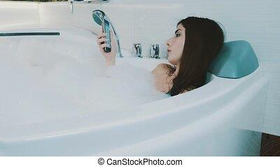Brunette girl relax in bath full of foam. Tap in smartphone. Enjoyment. Resting.