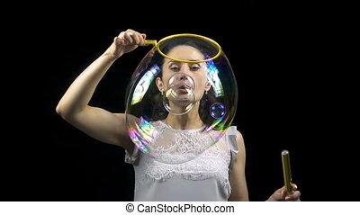 Brunette girl releasing soap bubbles