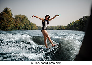 Brunette girl riding on the wakeboard keep her hands up