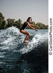 Brunette girl riding on the wakeboard on the bending knees