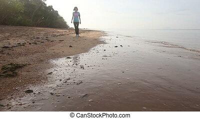 brunette girl runs along water edge at dawn