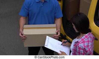 Brunette girl sign papaer for package delivery - Look From...