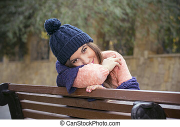brunette girl sitting on a bench in autumn