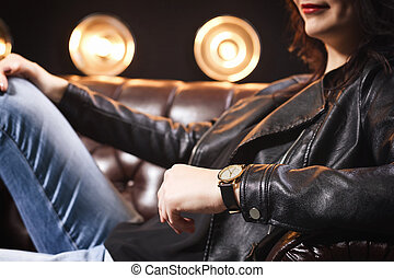 brunette girl sitting on couch in the studio, close up