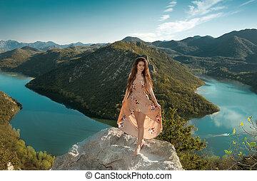Brunette girl tourist in dress sightseeing of Rijeka Crnojevica, Montenegro. Skadar lake national park, Pavlova Strana. Viewpoint Ridge mountains panoramaic landscape.