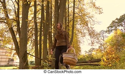 Brunette girl walking in autumn forest holding a basket. 4K steadicam clip