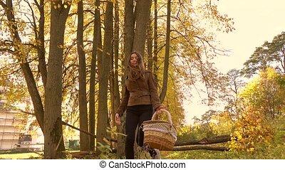 Brunette girl walking in autumn forest holding a basket. 4K steadicam clip