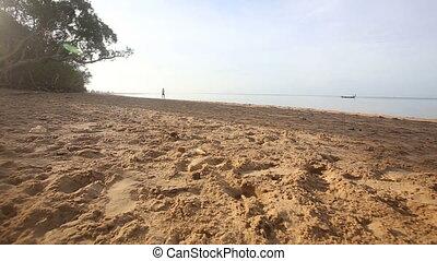 brunette girl walks on beach at dawn