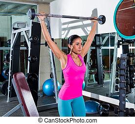 brunette girl wide grip barbell shoulder press gym