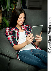 Brunette girl with a tablet at home