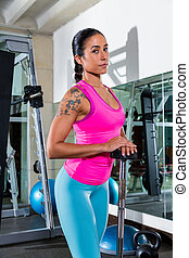 brunette girl with barbell posing at gym