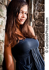 Brunette girl with big breast leaning against brick wall