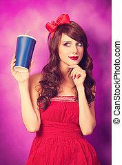Brunette girl with bottle on violet background.