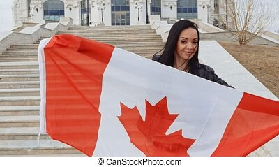Brunette girl with Canada Flag in Her Hands Smiling posing...
