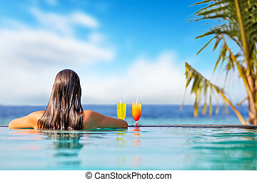 Brunette girl with cocktails in swimming pool